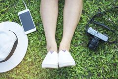 Asain tourist woman wear white shoes sitting for relaxing with white hat, camera and smartphone on a green grass at the park, Royalty Free Stock Photography