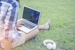 Asain woman wearing a shirt sitting on the green grass while typing Thai keyboard of laptop put on the leg with the ear plug for r Stock Image