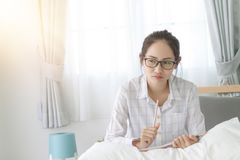 Asain woman writing on bed Stock Images