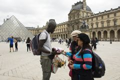 Asain women mother and daughter buying souvenir gift from African-French Royalty Free Stock Images