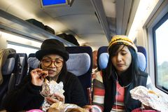 Asain women mother and daughter eating snack and listen music on mobile phone on train Stock Photo