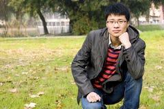 Asain young man in park. Asain young man in autumn park,thinking pose Royalty Free Stock Photos
