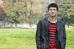 Asain young man in park. Asain young man in autumn park,smile Royalty Free Stock Photo