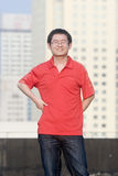 Asain young man smiles. Asain young man with red clothes smiles happily on the background of high buildings.Chinese young man is optimistic for the future Stock Photography
