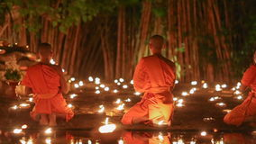 Asalha Puja Day , Chiang mai ,Thailand. Asalha Puja Day ,Monks light candles and pray to buddha statue in Phan tao temple , Chiang mai ,Thailand stock footage