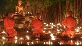 Asalha Puja Day , Chiang mai ,Thailand. Asalha Puja Day ,Monks light candles and pray to buddha statue in Phan tao temple , Chiang mai ,Thailand stock video footage