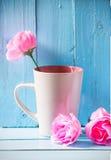 Asalte con las rosas rosadas en fondo de madera azul Imagen de archivo libre de regalías
