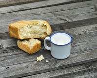 Asalte con leche y la barra de pan en la tabla vieja Foto de archivo libre de regalías