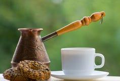 Asalte el café, las galletas y los potes de cobre al aire libre en fondo verde Fotos de archivo