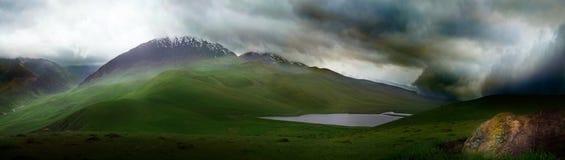 Asalte en las montañas Ile Alatau en día nublado, las colinas alpinas verdes y el lago de la moraine Imagen de archivo libre de regalías