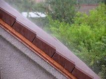 Asalte la lluvia en el tejado de la casa foto de archivo
