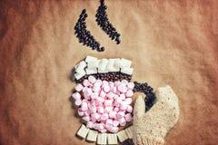Asalte la taza de cacao caliente del café de las melcochas y del café rosados del grano en viejo fondo de papel Imagen de archivo libre de regalías