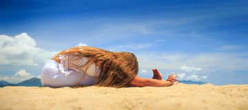 鞋带的女孩在瑜伽asana坚硬对膝盖向前弯坐 图库摄影