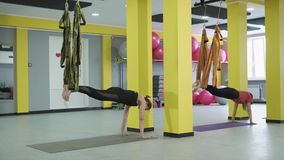 Asana of aerial yoga, performed in a semi-reclining position, supports on hands stock footage