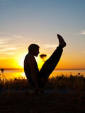 Asana d'esecuzione dell'uomo al tramonto Fotografia Stock