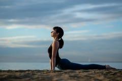 Asana de yoga dehors sur la plage vers le haut de faire face à la pose de chien Photo libre de droits