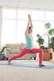 Asana di pratica di yoga della giovane donna sulla stuoia di yoga Fotografie Stock