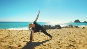 Asana di pratica di yoga dell'equilibrio della donna sulla costa del mare Ragazza di misura nella posa di yoga video d archivio