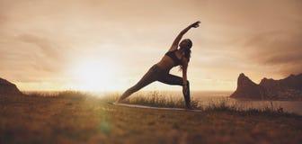 Asana di yoga di Utthita Parsvakonasana sulla scogliera al tramonto Immagini Stock