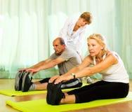 Asana för yogainstruktörvisning som mognar par Arkivbilder