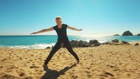 Asana practicante de la yoga de la mujer en la playa del mar Muchacha del ajuste que hace ejercicio de la flexibilidad metrajes