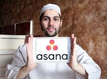 Asana software logo. Logo of Asana software on samsung tablet holded by arab muslim man. Asana is a web and mobile application designed to help teams track their Stock Image