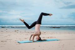 Asanas баланса практики молодой женщины на встрече йоги лета на пляже headstand Стоковые Изображения