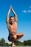 Счастливый атлетический человек делая asanas йоги в парке на солнечном дне Стоковое Изображение RF
