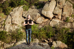 Asanas di pratica di yoga della bella ragazza allegra su roccia in canyon Fotografia Stock