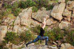 Asanas di pratica di yoga della bella ragazza bionda su roccia in canyon Immagini Stock Libere da Diritti