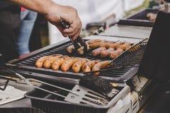 Asando a la parrilla las salchichas jugosas deliciosas de la carne en la parrilla grande al aire libre Imagenes de archivo