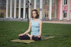 Asans doeing di yoga della giovane bella donna di misura sull'erba verde con la stuoia di yoga Fotografie Stock