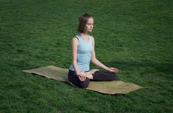 Asans doeing di yoga della giovane bella donna di misura sull'erba verde con la stuoia di yoga Fotografia Stock