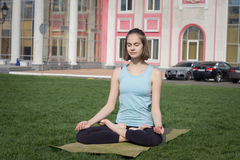 Asans doeing di yoga della giovane bella donna di misura sull'erba verde con la stuoia di yoga Fotografie Stock Libere da Diritti