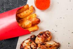 Asas de frango frito com batatas cozidas e molho do BBQ no papel do ofício no fundo preto imagem de stock royalty free