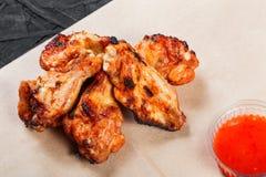 Asas de frango frito com batatas cozidas e molho do BBQ no papel do ofício no fundo preto Pratos quentes da carne fotografia de stock