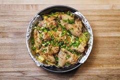 Asas de frango frito com cebolas verdes em uma superfície de madeira imagens de stock royalty free