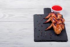 Asas de frango frito em uma placa preta com molho, fundo de madeira fotos de stock royalty free