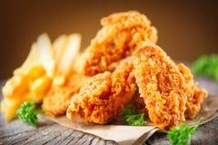 Asas de frango frito friáveis na tabela de madeira Fotos de Stock
