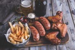 Asas de frango frito, molho grelhado das salsichas, das batatas fritas, das porcas, o branco e o vermelho alimento à cerveja imagem de stock