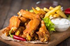 Asas de galinha com mergulhos na tabela de madeira Fotos de Stock