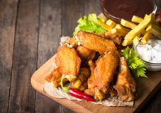Asas de galinha com mergulhos na tabela de madeira Foto de Stock