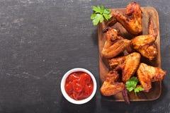 Asas de galinha cozidas na placa de madeira Imagens de Stock