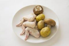 Asas de galinha cruas com batata e cogumelos Imagem de Stock Royalty Free