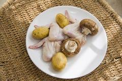 Asas de galinha cruas com batata e cogumelos: fundo rural da palha Imagens de Stock Royalty Free