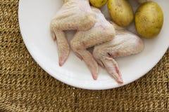 Asas de galinha cruas com a batata no fundo da palha Fotografia de Stock