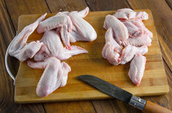 Asas de galinha cruas com a faca na madeira Imagens de Stock