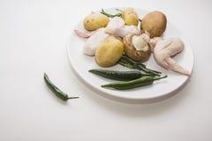 Asas de galinha cruas com pimentão e a batata verdes Imagem de Stock
