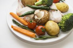 Asas de galinha cruas com vários vegetais Fotografia de Stock