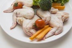 Asas de galinha cruas com vegetais Imagens de Stock Royalty Free